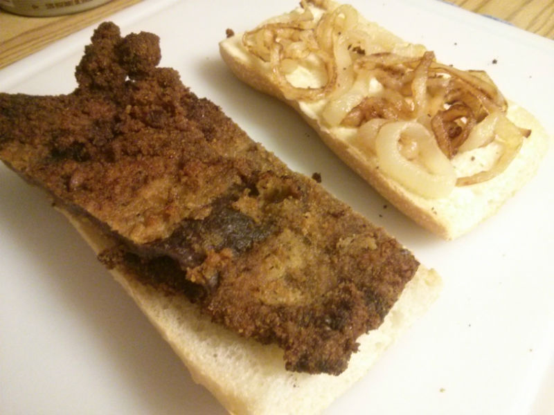 Place breaded steak and onions on cuban bread