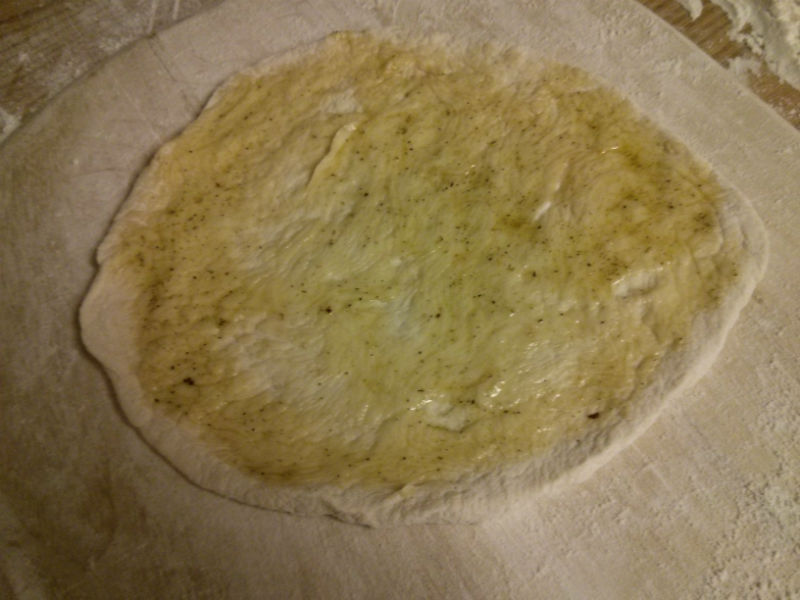 Pizza dough with olive oil & herb mixture spread evenly