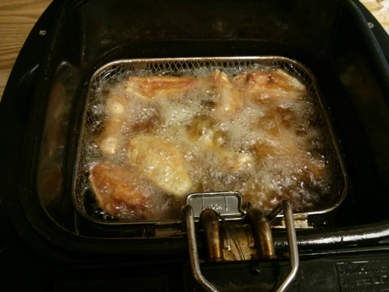 Chicken wings getting crispy in fryer